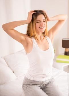 Giovane donna felice che sveglia a letto a casa.