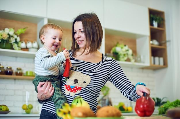 Giovane donna felice che tiene un bambino di 1 anno e che cucina insieme nella cucina