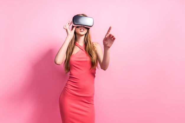 Giovane donna felice che usando una cuffia avricolare di realtà virtuale