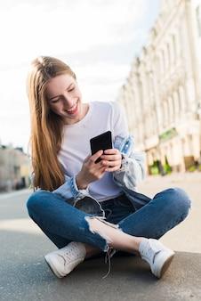 Giovane donna felice che utilizza smartphone che si siede sulla via