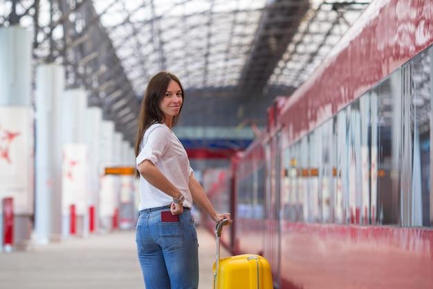 Giovane donna felice con bagagli gialli ad una stazione ferroviaria