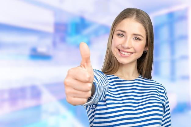 Giovane donna felice con i pollici in su