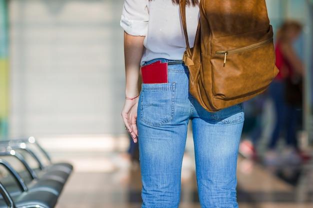 Giovane donna felice con il biglietto aereo e passaporti all'imbarco aspettante dell'aeroporto