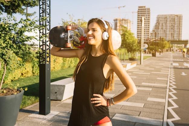 Giovane donna felice con il pattino che sta sul marciapiede