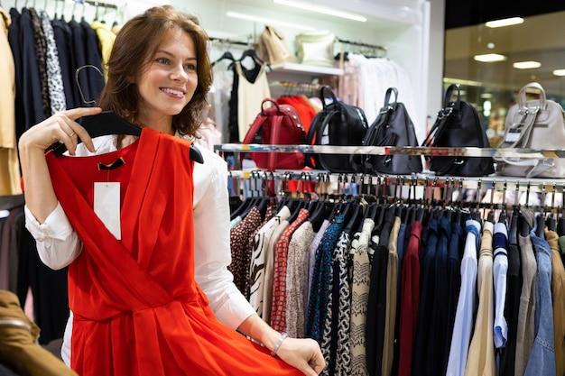 Giovane donna felice con l'acconciatura marrone che tiene il bello vestito da sera in sua mano