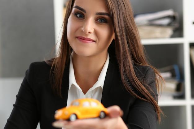 Giovane donna felice con l'automobile del giocattolo in ufficio