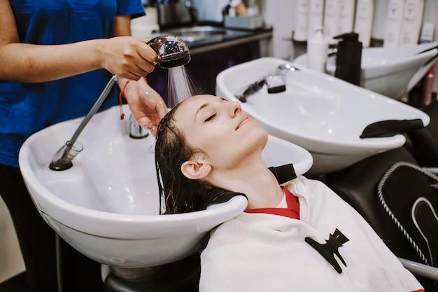 Giovane donna felice con la testa di lavaggio parrucchiere al parrucchiere