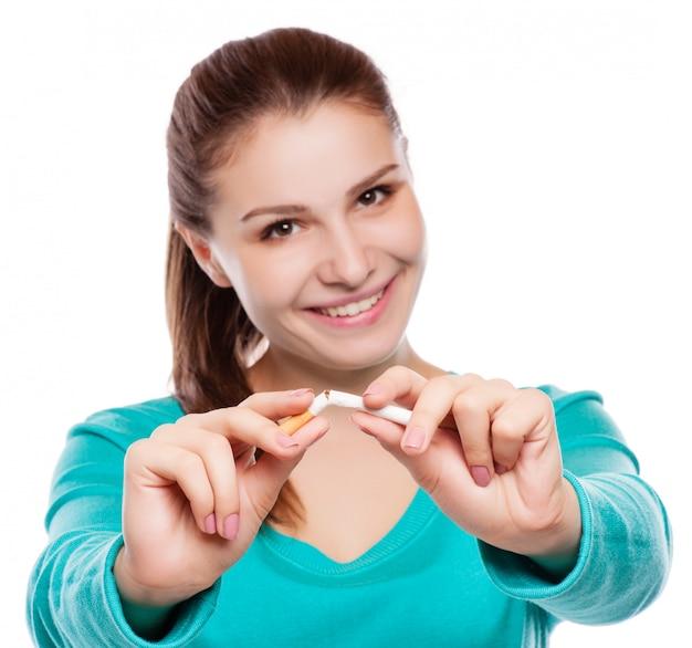 Giovane donna felice con sigaretta rotta. smetti di fumare.