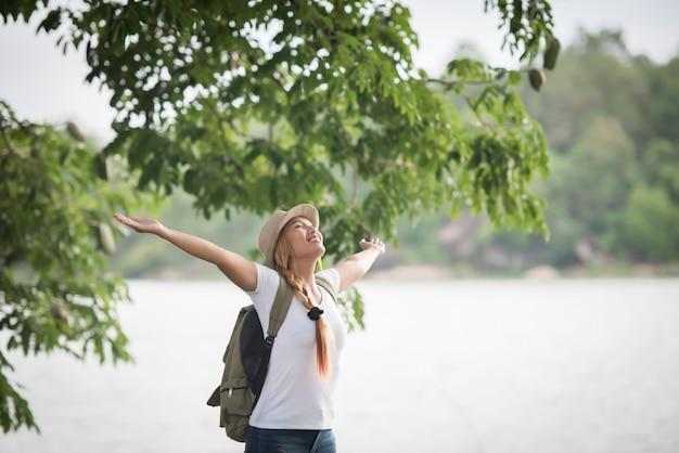 Giovane donna felice con zaino in piedi con le mani sollevate e guardando al fiume.