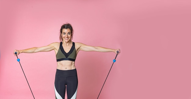 Giovane donna felice dei capelli del brunette con addestramento di stile di vita di forma fisica e fare allungando le esercitazioni con gli elastici