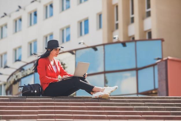 Giovane donna felice dei pantaloni a vita bassa che lavora agli outdors del computer portatile. ragazza dello studente che utilizza computer portatile nel campus universitario