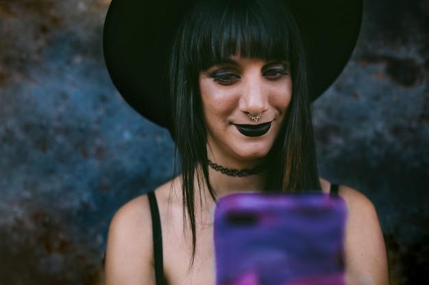 Giovane donna felice della strega di halloween che per mezzo dello smart phone. beauty strega con la bocca nera nell'oscurità, indossa un cappello da strega.
