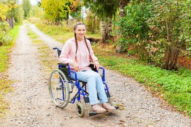 Giovane donna felice di handicap in sedia a rotelle sulla strada nel parco dell'ospedale che aspetta i servizi pazienti. ragazza paralizzata in sedia invalida per disabili all'aperto in natura. concetto di riabilitazione.