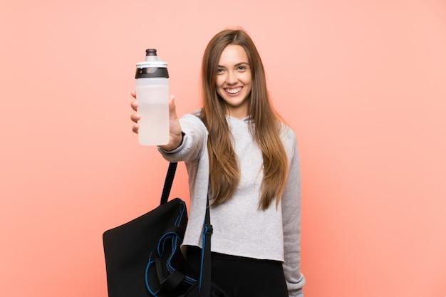 Giovane donna felice di sport sopra il rosa isolato con una bottiglia di acqua