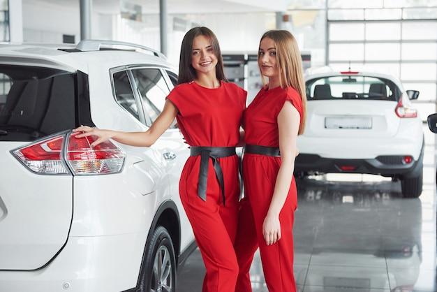 Giovane donna felice due vicino all'automobile con le chiavi a disposizione - concetto di automobile d'acquisto.
