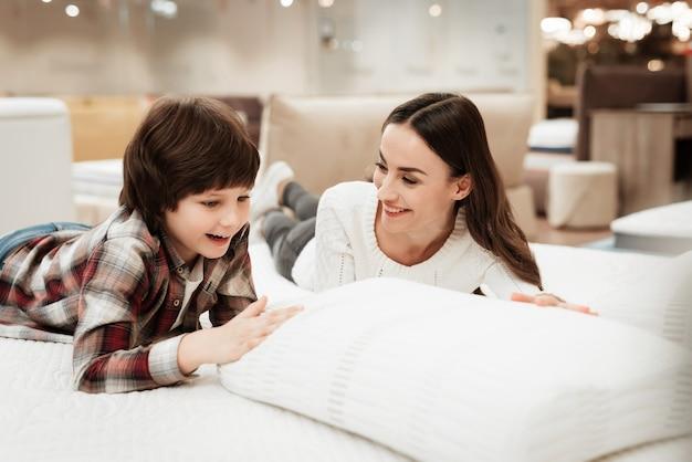 Giovane donna felice e ragazzino sul materasso