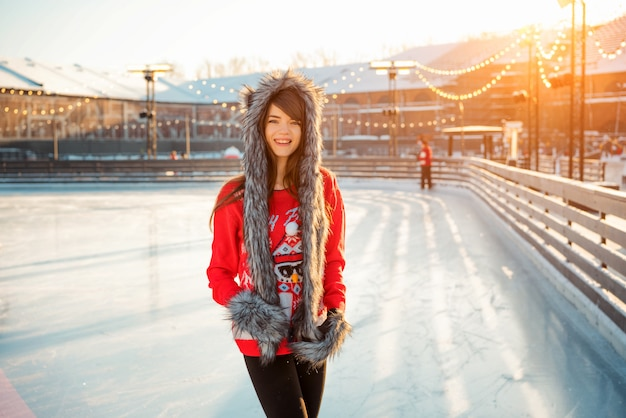 Giovane donna felice in cappello che pattina sul ghiaccio sulla strada