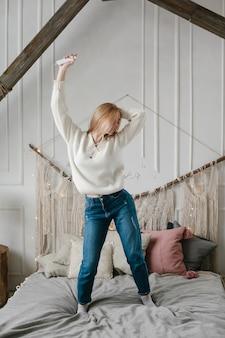 Giovane donna felice in cuffie che ascolta la musica dallo smartphone e che balla sul letto a casa