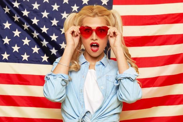 Giovane donna felice in occhiali da sole a forma di cuore su sfondo bandiera usa.
