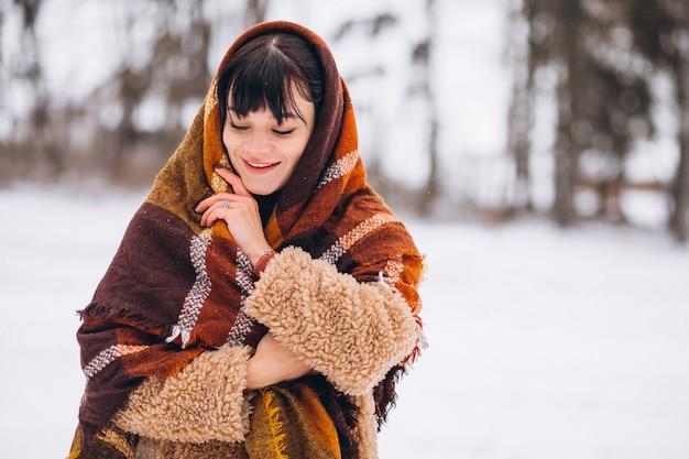 Giovane donna felice in panni caldi in un parco d'inverno