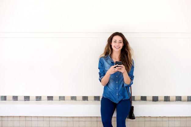 Giovane donna felice in piedi fuori con il cellulare