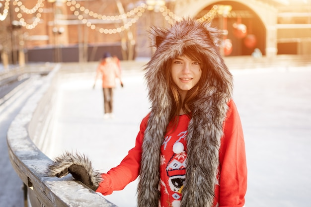 Giovane donna felice in un cappello di lupo in inverno presso la pista di pattinaggio