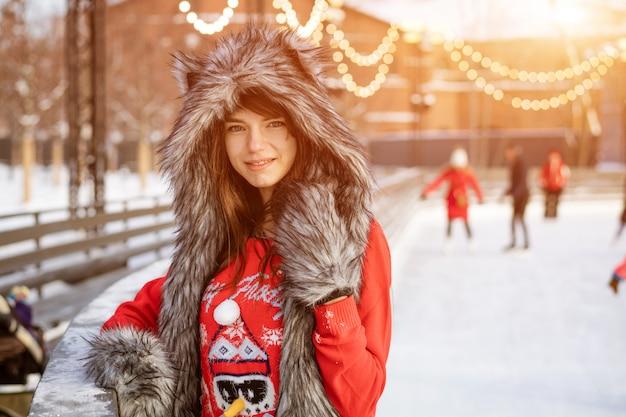 Giovane donna felice in un cappello di lupo in inverno sulla pista di pattinaggio sul ghiaccio in posa in un maglione rosso