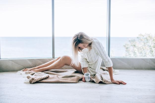 Giovane donna felice in un vestito lavorato a maglia bianco che gode della vista del mare vicino alla grande finestra con la tazza di tè e la risata. finestra panoramica. rivestimenti per pavimenti.