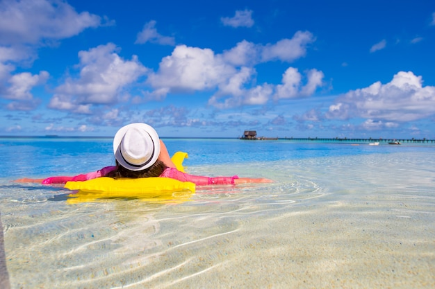 Giovane donna felice rilassante con materasso ad aria nella piscina