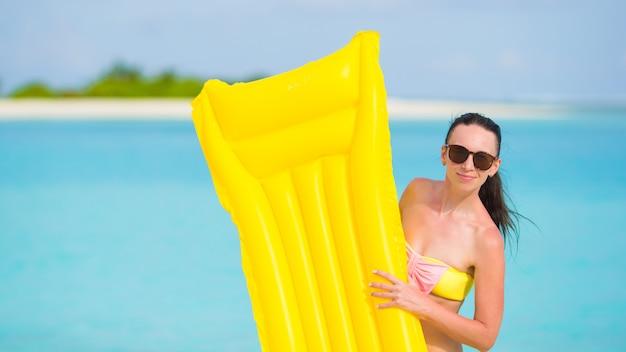 Giovane donna felice rilassante con materasso ad aria sulla spiaggia