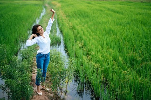 Giovane donna felicemente in un campo verde al giorno soleggiato