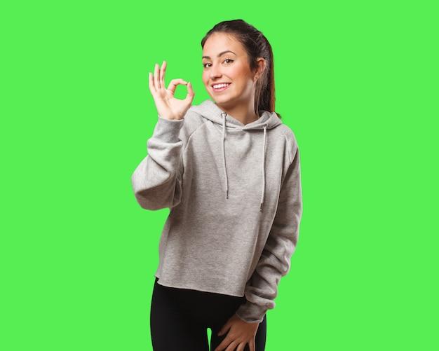 Giovane donna fitness allegro e fiducioso facendo gesto ok