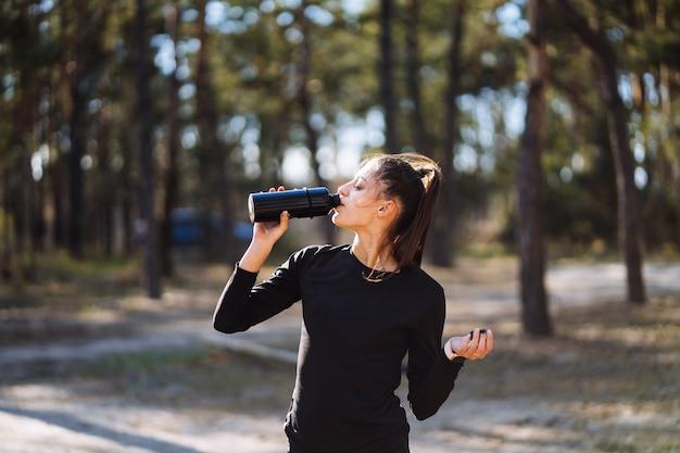 Giovane donna fitness cammina nel parco e in posa