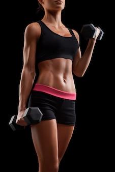 Giovane donna fitness in allenamento pompare i muscoli con manubri