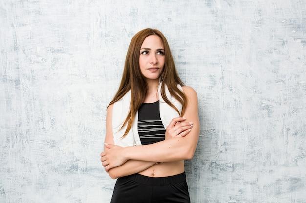 Giovane donna fitness sorridente fiducioso con le braccia incrociate.