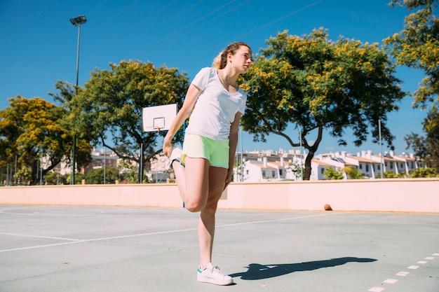 Giovane donna flessibile che scalda le gambe