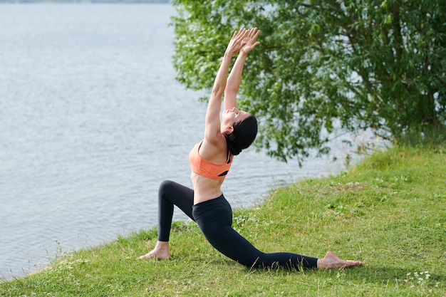 Giovane donna flessibile in leggings facendo un comodo tratto in posizione polmonare bassa e alzando le braccia all'aperto