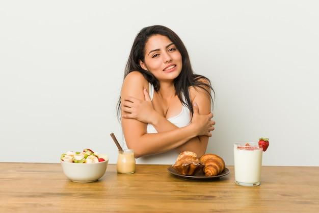 Giovane donna formosa che fa colazione facendo freddo a causa della bassa temperatura o di una malattia.