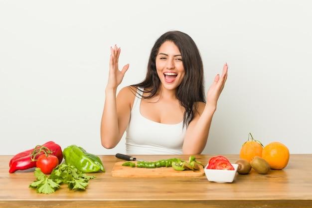 Giovane donna formosa che prepara un pasto sano ricevendo una piacevole sorpresa, eccitata e alzando le mani.