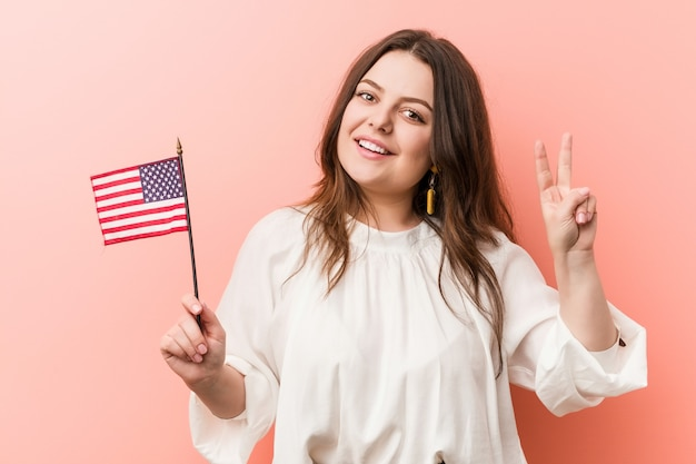 Giovane donna formosa e taglie forti che tiene una bandiera degli stati uniti che mostra il segno di vittoria e che sorride ampiamente.