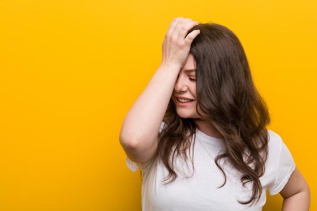 Giovane donna formosa più grande che dimentica qualcosa, battendo la fronte con il palmo e chiudendo gli occhi.