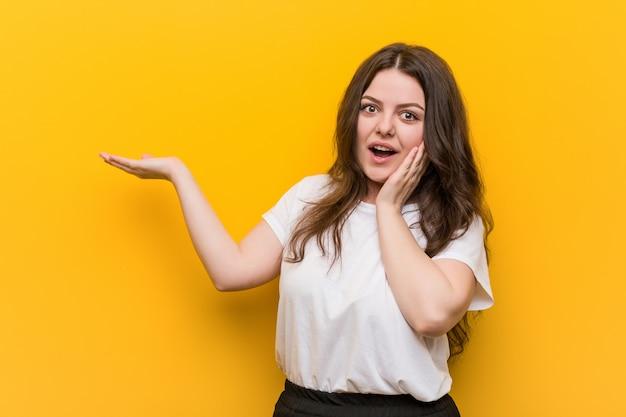 Giovane donna formosa plus size detiene lo spazio di copia su un palmo, tenere la mano sulla guancia. stupito e felice.