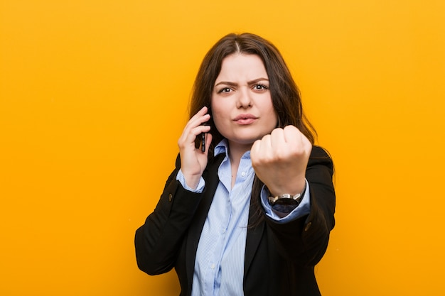 Giovane donna formosa plus size in possesso di un telefono che mostra il pugno, espressione facciale aggressiva.