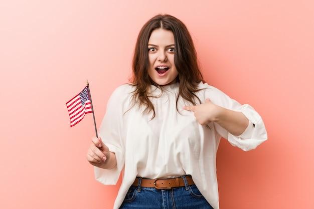 Giovane donna formosa plus size in possesso di una bandiera degli stati uniti sorpreso indicando se stesso, sorridendo ampiamente.