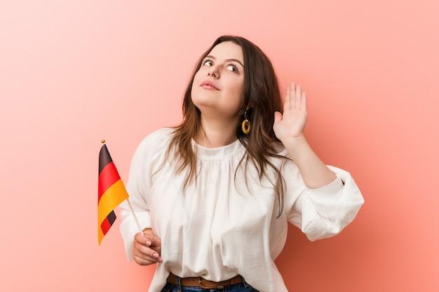 Giovane donna formosa plus size in possesso di una bandiera della germania cercando di ascoltare un gossip.