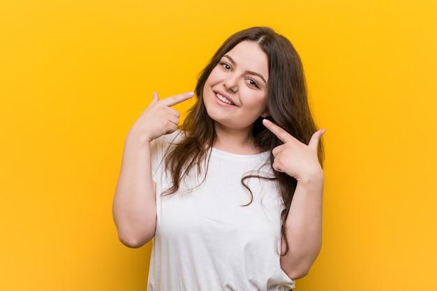 Giovane donna formosa plus size sorride, indicando le dita in bocca.