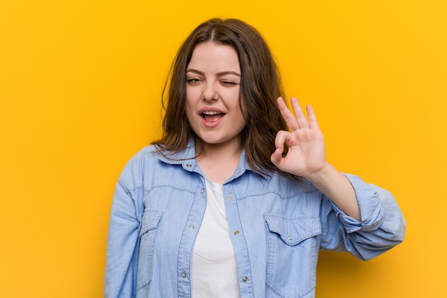 Giovane donna formosa plus size strizza l'occhio e tiene un gesto ok con la mano.