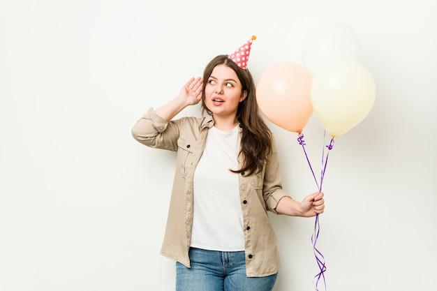 Giovane donna formosa taglie forti che celebra un compleanno cercando di ascoltare un gossip.