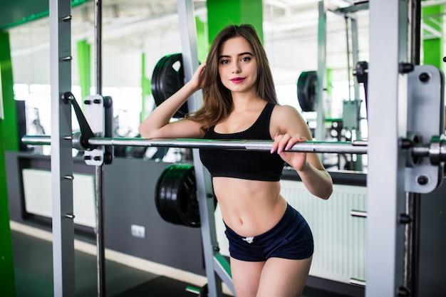 Giovane donna forte abbastanza allegra che fa le esercitazioni con il bilanciere agghindato in abiti sportivi di modo in sportclub