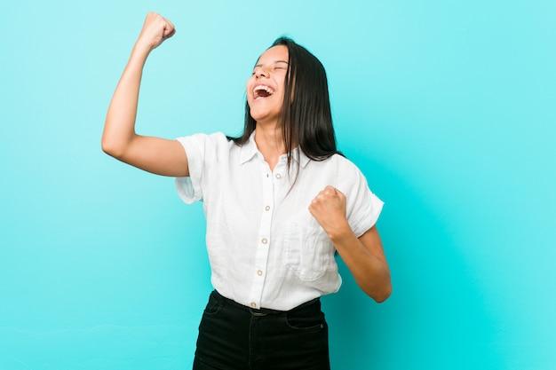 Giovane donna fredda ispanica contro una parete blu che alza pugno dopo una vittoria, concetto del vincitore.
